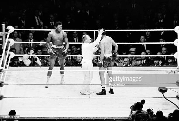 Referee George Smith examines Henry Cooper's badly damaged eye during the World Heavyweight title fight against Muhammad Ali at Highbury Stadium in...