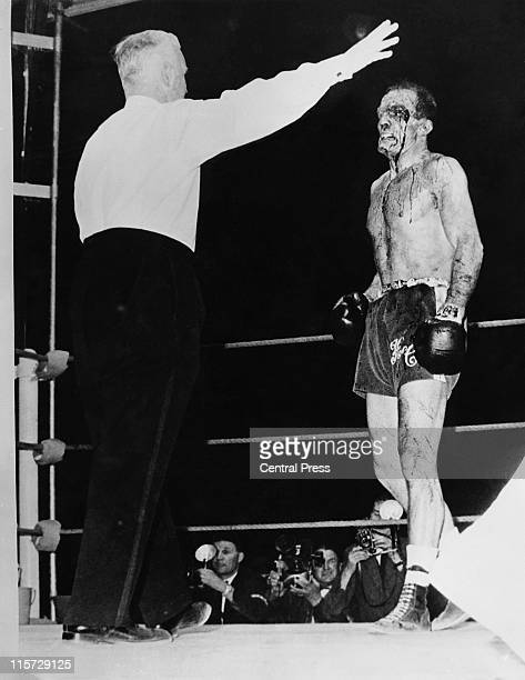 Referee George Smith stops the World Heavyweight title fight between British boxer Henry Cooper and American boxer Cassius Clay after Cooper...
