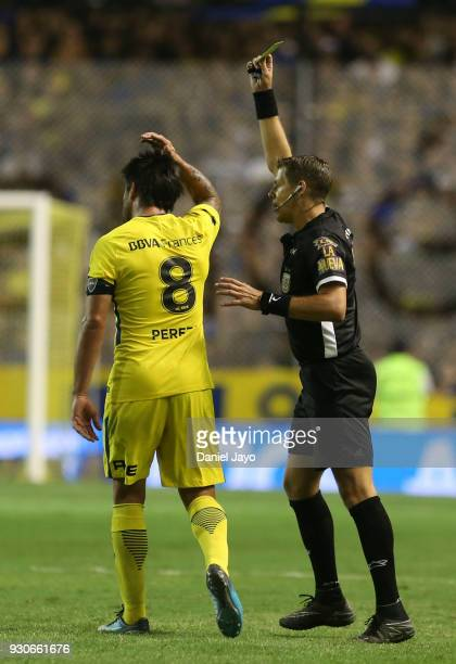 Referee German Delfino issues a yellow card to Edwin Cardona of Boca Juniors during a match between Boca Juniors and Tigre as part of the Superliga...