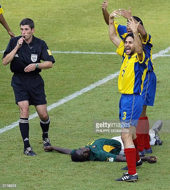 referee German Markus Merk and Colombian defender Mario Yepes call medics as Cameroonian midfielder MarcVivien Foe lies on the field during their...