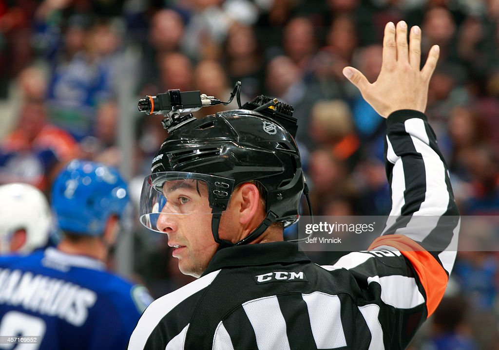 Referee Ghislain Hebert wears a video camera on his helmet during the NHL game between the Vancouver Canucks and the Edmonton Oilers at Rogers Arena October 11, 2014 in Vancouver, British Columbia, Canada. Vancouver won 5-4 in a shootout.