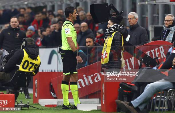 Referee Gianluca Manganiello consult the VAR during the Serie A match between AC Milan and US Sassuolo at Stadio Giuseppe Meazza on December 15, 2019...