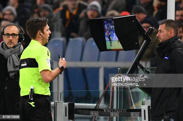 Referee Gianluca Rocchi checks the Video assistant referee during the Italian Serie A football match AS Roma vs Lazio on November 18 2017 at the...