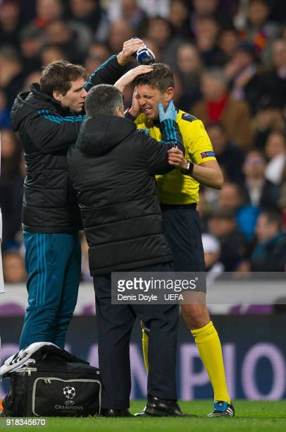 Referee Gianluca Rocchi is attended after being hit by the ball during the UEFA Champions League Round of 16 First Leg match between Real Madrid and...