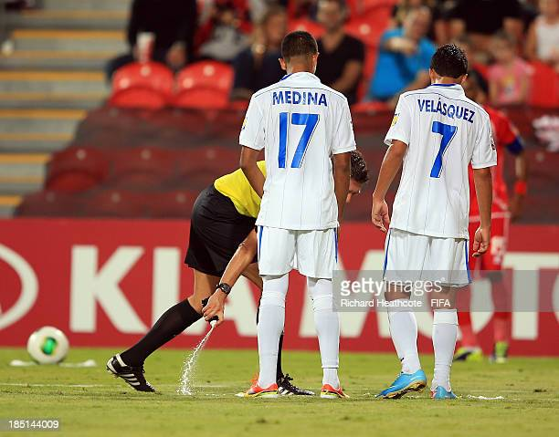 Referee Gianluca Rocchi of Italy marks out the wall's distance from the freekick with spray during the FIFA U17 World Cup UAE 2013 group A match...