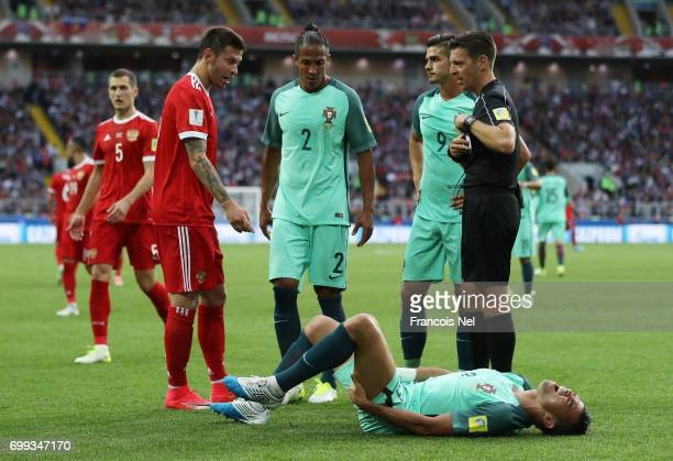 Referee Gianluca Rocchi reaches for a card as Pepe of Portugal si down injured on the floor during the FIFA Confederations Cup Russia 2017 Group A...