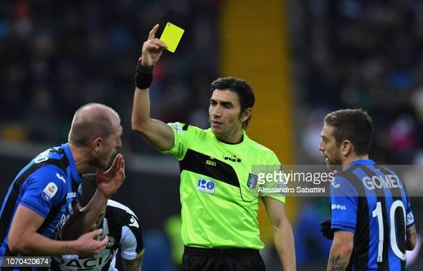 Referee Gianpaolo Calvarese shows the yellow card to Andrea Masiello of Atalanta BC during the Serie A match between Udinese and Atalanta BC at...