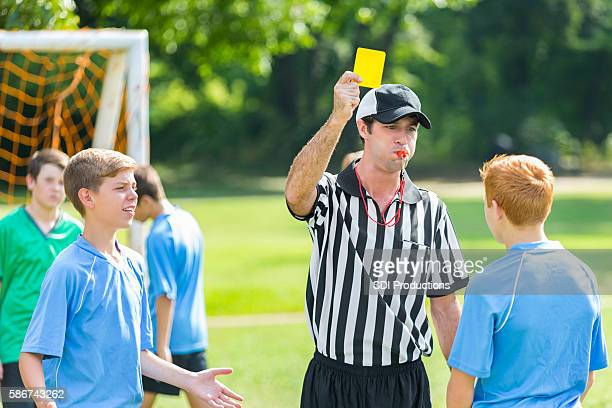 referee gives out yellow card during soccer game - yellow card stock pictures, royalty-free photos & images