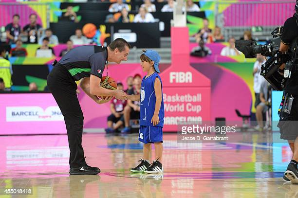 A referee gives the ball to a kid prior to the game of the USA Basketball Men's National Team against the Slovenia National Team during the 2014 FIBA...