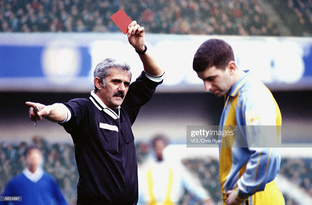 Referee giving a soccer player a red card : Stockfoto