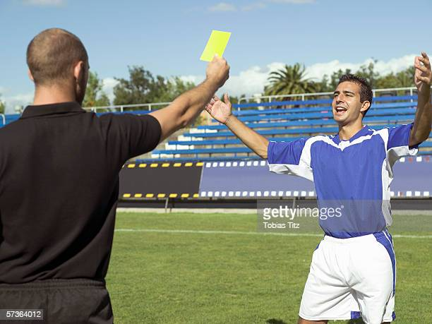 a referee giving a soccer player a yellow card - yellow card stock pictures, royalty-free photos & images