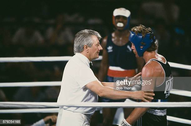 Referee Gligorije Novicic of Yugoslavia checks on Kevin Barry of New Zealand after he was knocked down by Evander Holyfield of the USA in the second...