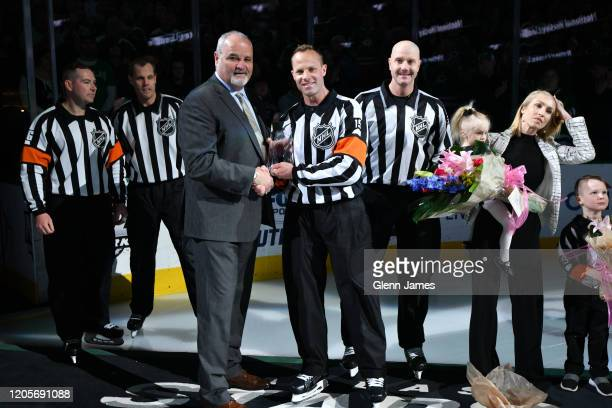 Referee Gord Dwyer is presented with a tiffany crystal by NHL Officiating Manager Don Van Massenhoven as he celebrates his 1000th NHL game alongside...