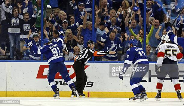 Referee Gord Dwyer signals a goal as Steven Stamkos and Alex Killorn of the Tampa Bay Lightning celebrate as Jason Demers of the Florida Panthers...