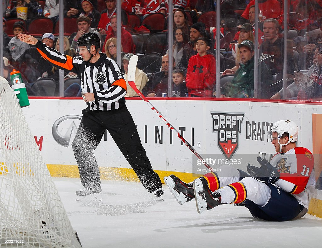 Referee Gord Dwyer #19 signals for a penalty shot after Jonathan Huberdeau #11 of the Florida Panthers was taken down on a breakaway by Adam Larsson #5 (not pictured) of the New Jersey Devils during the game at the Prudential Center on December 6, 2015 in Newark, New Jersey.