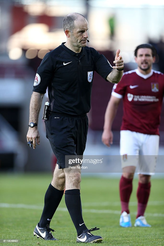 Referee Graham Horwood motions to the bench prior to leaving the pitch with an injury during the Sky Bet League One match between Northampton Town and Bristol Rovers at Sixfields Stadium on October 1, 2016 in Northampton, England.