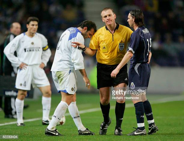 Referee Graham Poll breaks up Cristiano Zanetti of Inter Milan and Maniche of Porto during The UEFA Champions League knockout stage 1st leg match...
