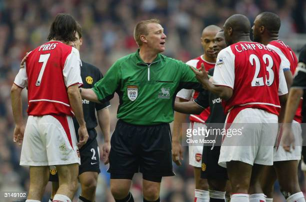 Referee Graham Poll holds apart Arsenal and Manchester United players during the FA Barclaycard Premiership match between Arsenal and Manchester...