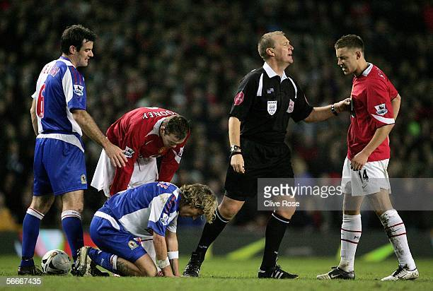 Referee Graham Poll restrains Manchester's Alan Smith after he is shown a yellow card for fouling Robbie Savage of Blackburn during the Carling Cup...