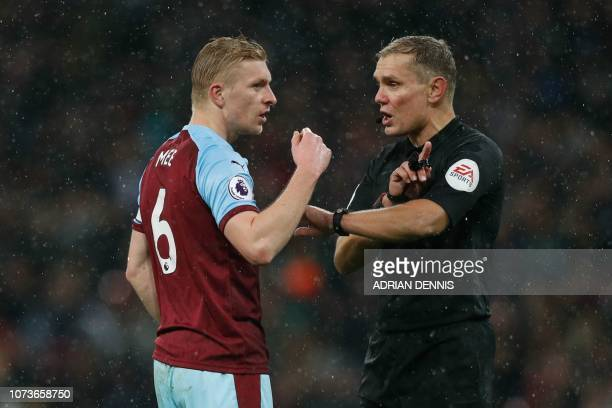 Referee Graham Scott gives a warning to Burnley's English defender Ben Mee during the English Premier League football match between Tottenham Hotspur...