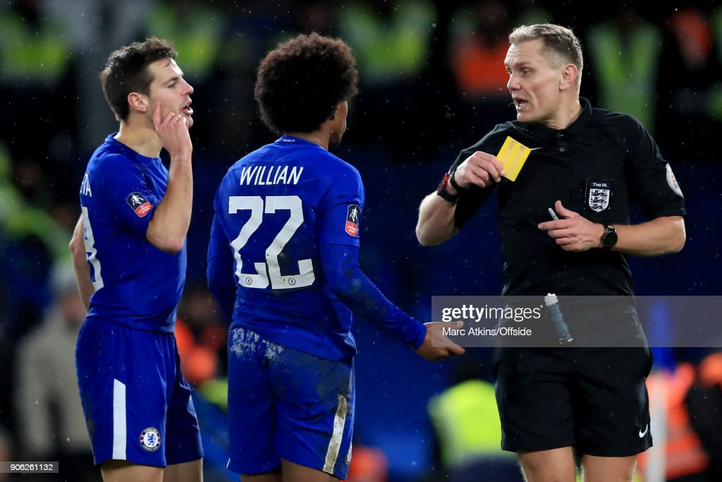 Referee Graham Scott is confronted by Cesar Azpilicueta as he shows a yellow card to Willian of Chelsea for simulation during the Emirates FA Cup Third Round Replay match between Chelsea and Norwich City at Stamford Bridge on January 17, 2018 in London, England.