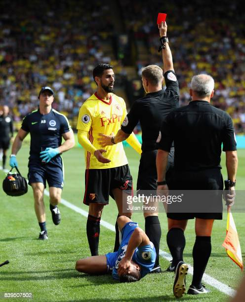 Referee Graham Scott shows a red card to Miguel Britos of Watford during the Premier League match between Watford and Brighton and Hove Albion at...