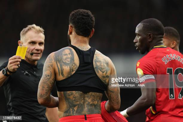 Referee Graham Scott shows a yellow card to Joshua King of Watford after he took off his shirt to reveals his tattoos as he celebrated after scoring...