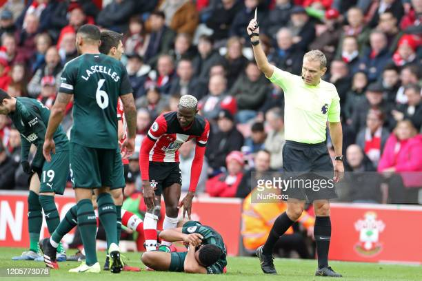 Referee Graham Scott shows a yellow card to Southampton forward Moussa Djenepo during the Premier League match between Southampton and Newcastle...