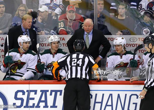 Referee Graham Skilliter gives an explanation to Head Coach Bruce Boudreau of the Minnesota Wild during a second period stoppage against the Winnipeg...