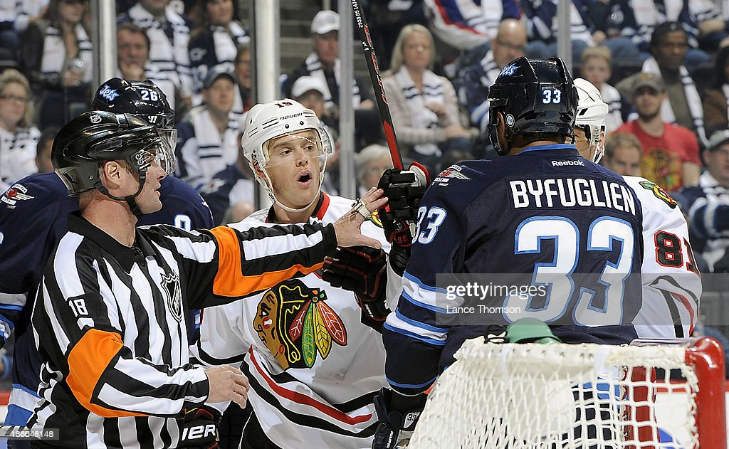 Referee Greg Kiimmerly #18 separates Jonathan Toews #19 of the Chicago Blackhawks and Dustin Byfuglien #33 of the Winnipeg Jets during a third period scrum at the MTS Centre on November 2, 2013 in Winnipeg, Manitoba, Canada.