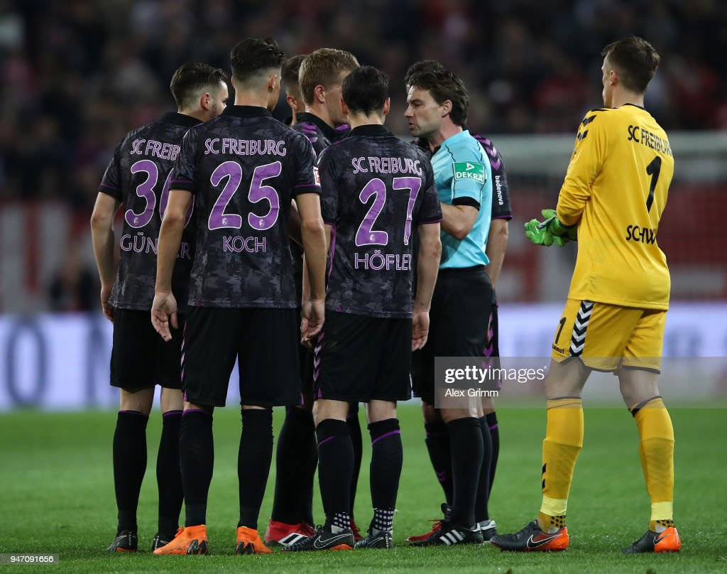 Referee Guido Winkmann explains to the players of Freiburg his decision to recall the teams and award a penalty before half time during the Bundesliga match between 1. FSV Mainz 05 and Sport-Club Freiburg at Opel Arena on April 16, 2018 in Mainz, Germany.