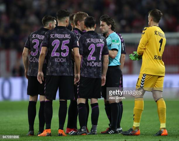 Referee Guido Winkmann explains to the players of Freiburg his decision to recall the teams and award a penalty before half time during the...