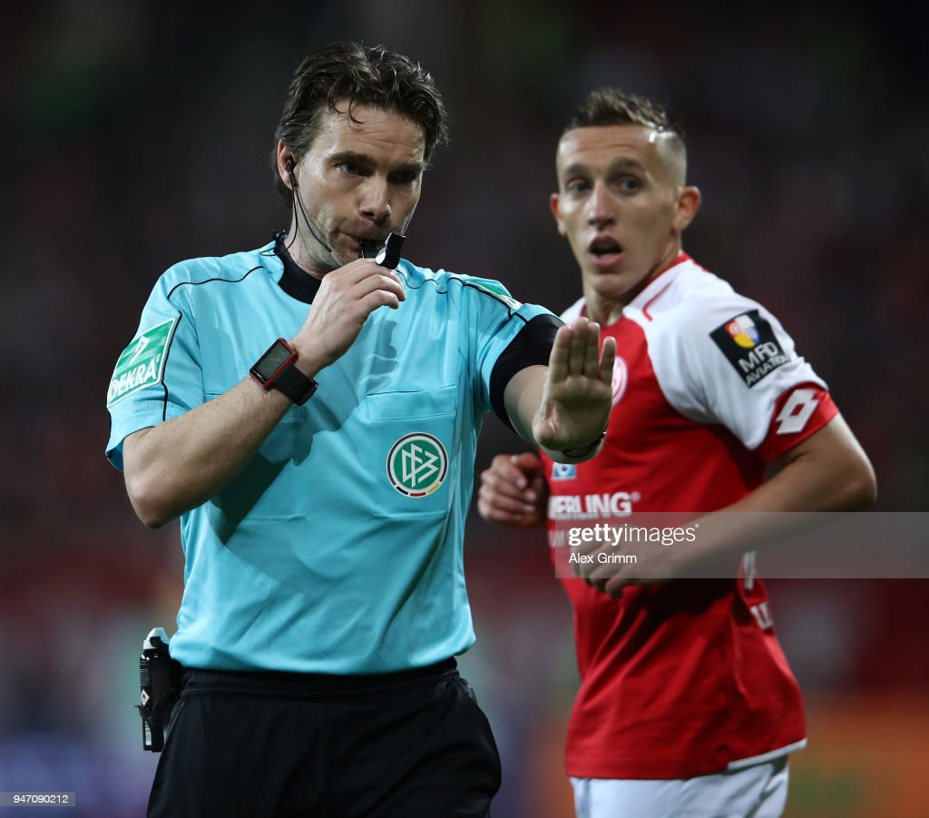 Referee Guido Winkmann gestures as goal scorer Pablo de Blasis of Mainz looks on during the Bundesliga match between 1. FSV Mainz 05 and Sport-Club Freiburg at Opel Arena on April 16, 2018 in Mainz, Germany.