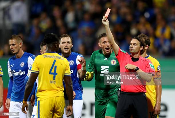 Referee Guido Winkmann shows the red card to Joseph Baffo of Braunschweig during the DFB Cup first round match between Holstein Kiel and Eintracht...