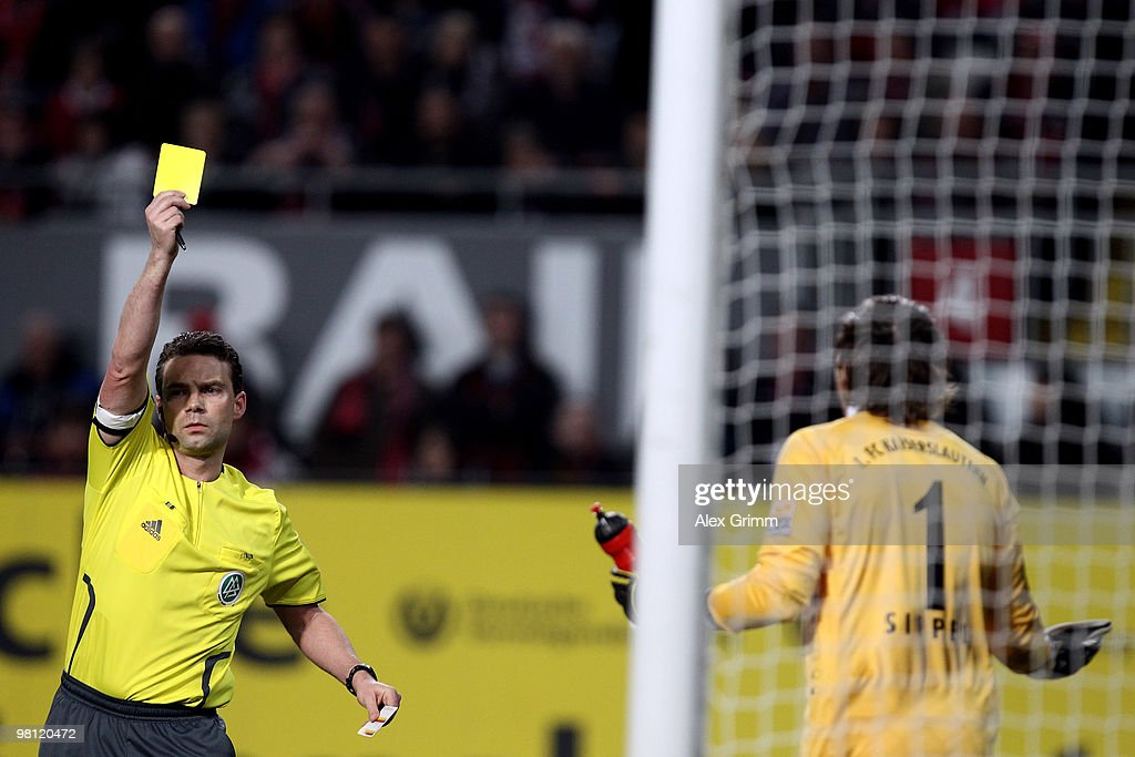 Referee Guido Winkmann shows the yellow card to goalkeeper Tobias Sippel of Kaiserslautern during the Second Bundesliga match between 1. FC Kaiserslautern and 1860 Muenchen at the Fritz-Walter Stadium on March 29, 2010 in Kaiserslautern, Germany.