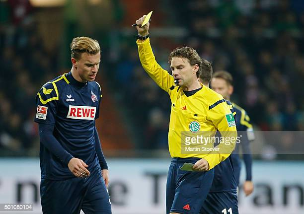 Referee Guido Winkmann shows the yellow card to Kevin Vogt of Koeln during the Bundesliga match between Werder Bremen and 1 FC Koeln at Weserstadion...