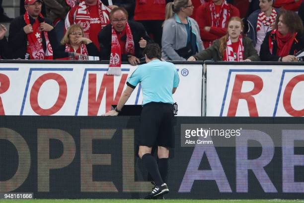 Referee Guido Winkmann watches the VAR screen before calling a hand penalty after the half time whistle during the Bundesliga match between 1 FSV...