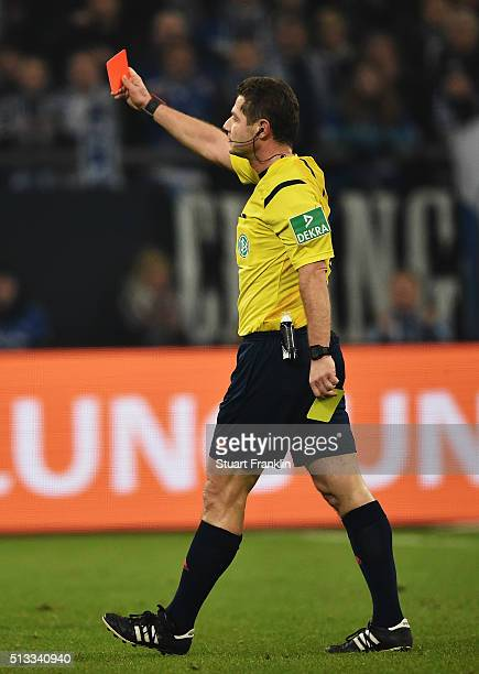 Referee Gunter Perl shows the red card during the Bundesliga match between FC Schalke 04 and Hamburger SV at VeltinsArena on March 2 2016 in...