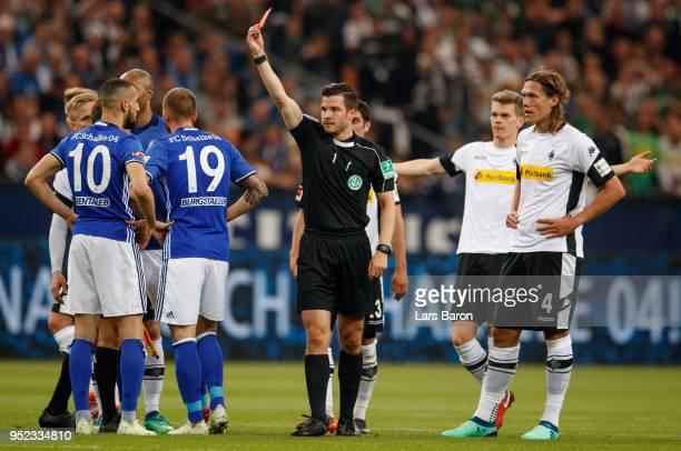 Referee Harm Osmars shows Nabil Bentaleb of Schalke the red card during the Bundesliga match between FC Schalke 04 and Borussia Moenchengladbach at...