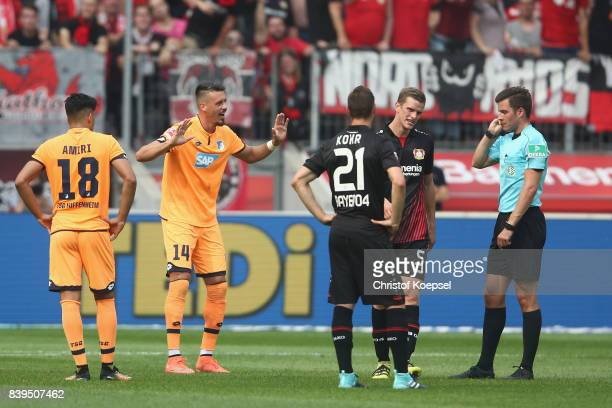 Referee Harm Osmers awaits a video decision for a penalty with Sandro Wagner of Hoffenheim during the Bundesliga match between Bayer 04 Leverkusen...