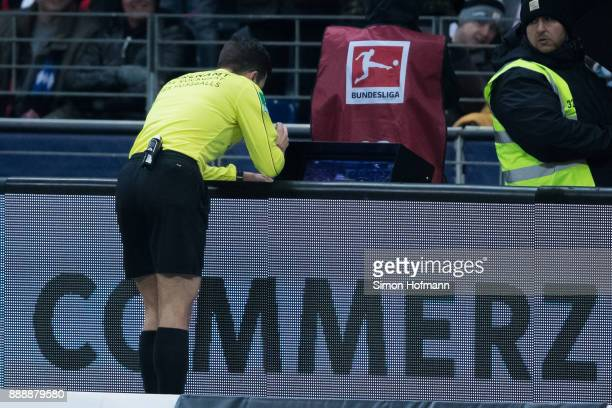 Referee Harm Osmers checks the video assistant screen during the Bundesliga match between Eintracht Frankfurt and FC Bayern Muenchen at...