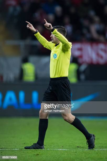 Referee Harm Osmers gestures to show he was in contact with the video assistant referee during the Bundesliga match between Eintracht Frankfurt and...
