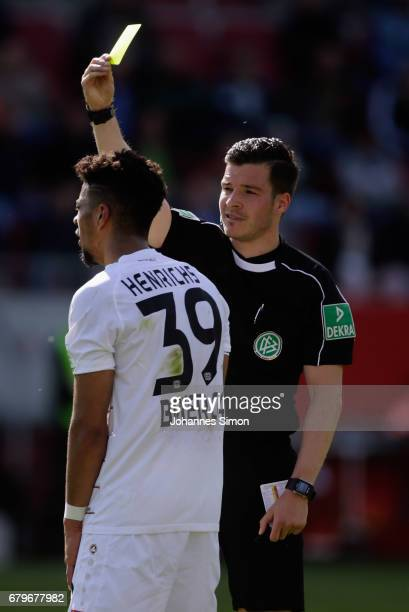 Referee Harm Osmers presents the yellow card to Benjamin Henrichs of Leverkusen fight for the ball during the Bundesliga match between FC Ingolstadt...