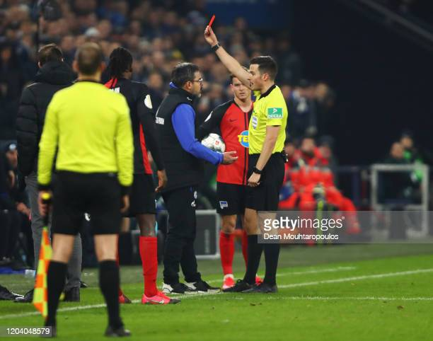 Referee Harm Osmers shows a red card to David Wagner Head Coach of FC Schalke 04 during the DFB Cup round of sixteen match between FC Schalke 04 and...