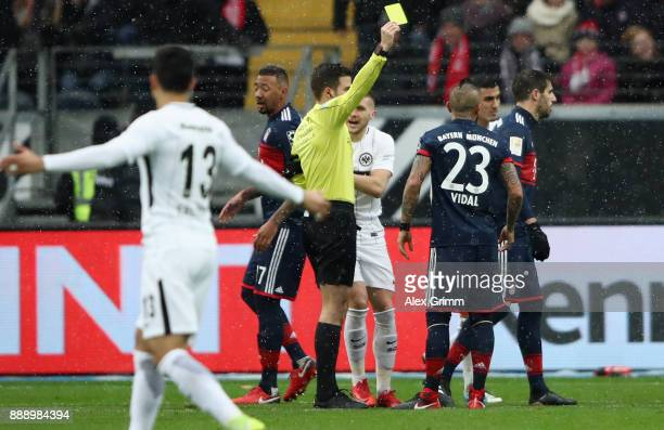 Referee Harm Osmers shows the yellow card to Arturo Vidal of Muenchen during the Bundesliga match between Eintracht Frankfurt and FC Bayern Muenchen...