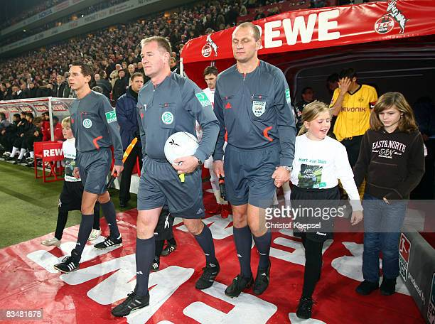 Referee Helmut Fleischer enters the pitch with linesman Christian Bandurski and linesman Soenke Glindemann before the 150th game during the...