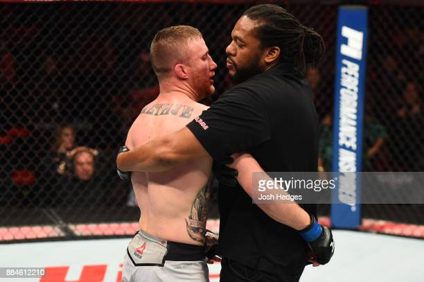 Referee Herb Dean holds back Justin Gaethje after he was knocked out by Eddie Alvarez in their lightweight bout during the UFC 218 event inside...