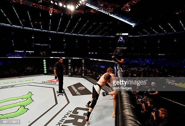 Referee Herb Dean looks on as Daniel Kelly and Steve Montgomery wrestle for position in their middleweight bout during the UFC 193 event at Etihad...