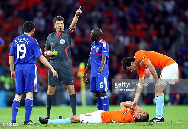 Referee Herbert Fandel of Germany shows a yellow card to Claude Makelele of France as Rafael van der Vaart of Netherlands lies on the ground during...