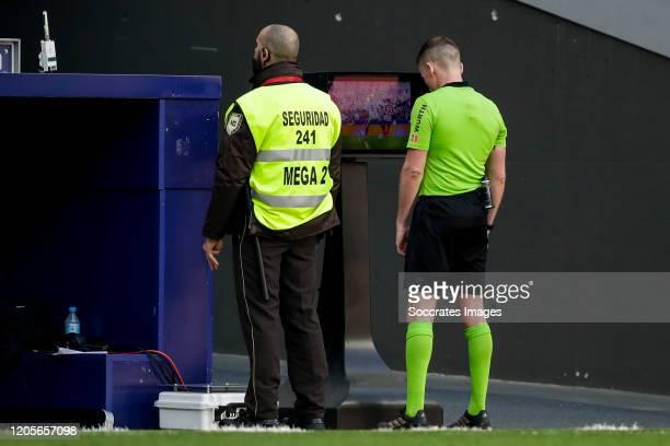 Referee Hernandez Hernandez is looking at the VAR screen during the La Liga Santander match between Atletico Madrid v Sevilla at the Estadio Wanda...